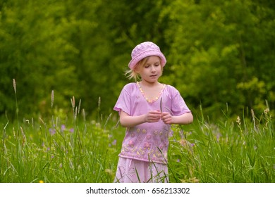 Adorable blonde girl in  pink hat and clothes posing on sunset on meadow with flowers