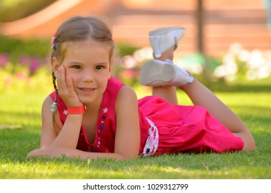 Adorable blonde girl in red dress lying on the grass in park on a sunny summer day