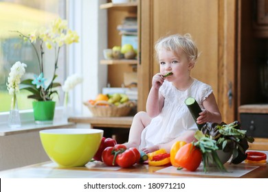 Adorable blonde toddler girl in beautiful white dress eating cucumber preparing healthy vegetables salad sitting on the table in sunny kitchen with big garden view window
