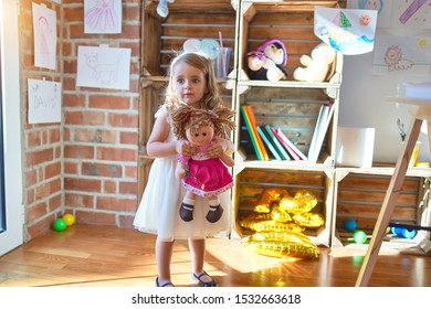 Adorable blonde toddler hugigng doll around lots of toys at kindergarten