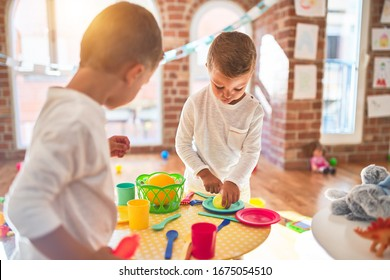 Adorable blonde twins playing around lots of toys. Cooking plastic food toy at kindergarten