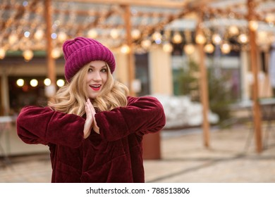 Adorable  blonde woman wearing red knitted hat and winter coat, posing on the background of garland at the street in Kyiv