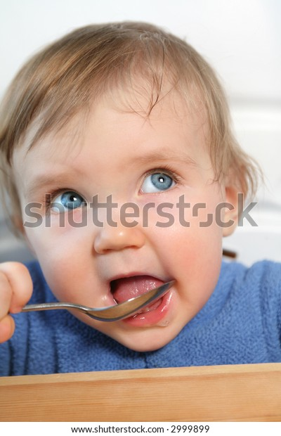 adorable blue eyed baby eating from a spoon