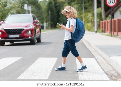 Adorable boy with a backpack, headphones and cellphone goes through the pedestrian crossing, not looking at red cars let him through