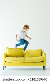 adorable boy in casual clothes jumping on yellow sofa on white