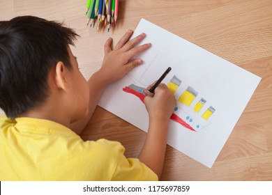 Adorable boy doing homework, color pencil on pages, writing and painting the titanic boat.