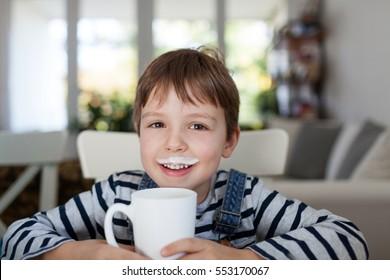 Adorable boy drinking milk or yogurt, shallow depth of field