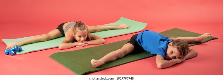 Adorable boy and girl doing the splits against red background