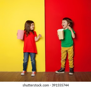 Adorable boy and girl having great time eating popcorn, on red and yellow background