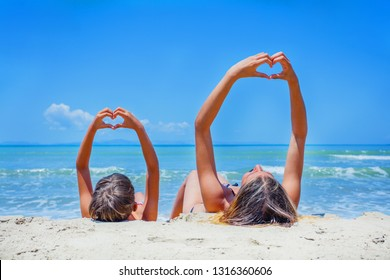 Adorable boy and girl playing on the beach on summer holidays. Children in nature with beautiful sea, sand and blue sky.