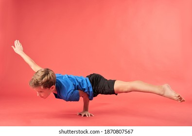 Adorable boy gymnast doing one arm handstand exercise