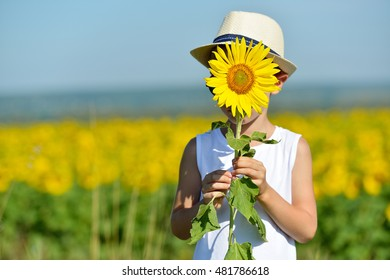 Adorable boy in hat hiding behind sunflower on yellow field outdoors. Kids portrait. Summer countryside agriculture