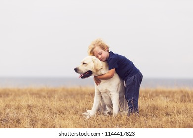 adorable boy hugging her labrador retriever. happy kid with big white dog outdoors. child and his dog best friend having fun in the garden. toddler boy with cute family dog.