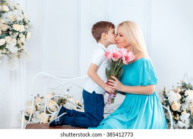 adorable boy kissing his mother on the cheek and gives her a bouquet of pink tulips, Mother's Day, 8 March