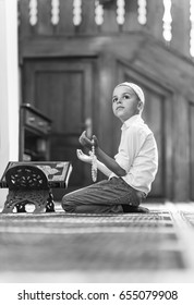 adorable boy Muslim is praying in mosque