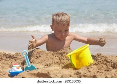 Adorable boy play on the beach with sand