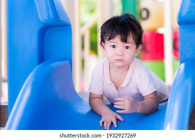 Adorable boy played the blue slider. Toddler play in the playground. During the summer or spring. Child looking at the camera, 1-2 years old.