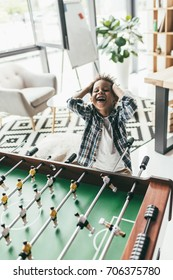 adorable boy playing table football and holding head