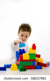 Adorable boy playing toy blocks inside his house