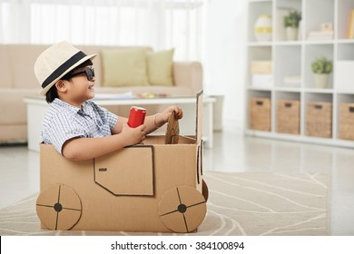 Adorable boy pretending to drive a cardboard car