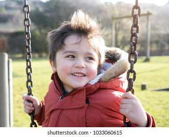 Adorable boy sitting on swing with smilng face in the park on sunshine day,Toddler having fun with swing chair at the playground on spring time, Active child playing outside in the sunny day