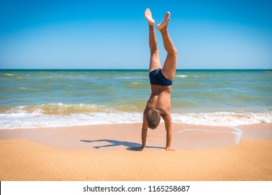 Adorable boy standing upside down on the beach