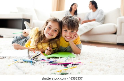 Adorable brother and sister drawing lying on the floor in the living room