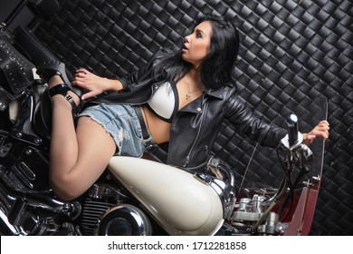 Adorable brunette dressed in a leather jacket and shorts sitting on a motorcycle