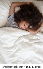 Adorable calm little african girl with raised hands sleeping under warm white blanket in bed during day nap at home or kindergarten close up image from top, rest of body mind, care of health concept