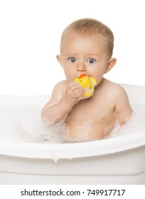 Adorable caucasian baby boy in a white bathtub with bubble bath. The kid is playing with a yellow rubber duck.