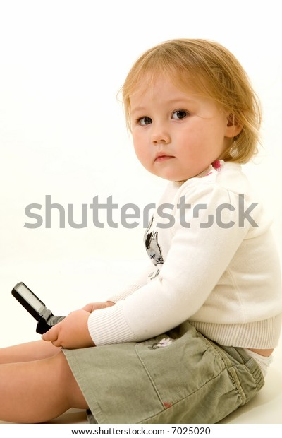Adorable caucasian blond baby girl toddler sitting on the floor holding a text message pager