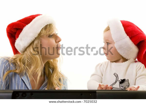 Adorable caucasian blond baby girl toddler sitting with mom both wearing Santa caps looking at each other