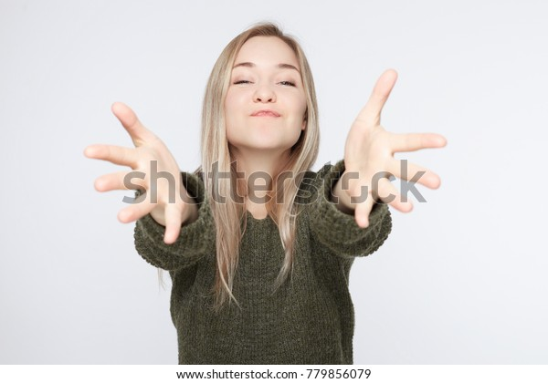 Adorable Caucasian blonde woman looking with great disbelief directly into camera, keeping arms wide open while being surprised with lovely present of her boyfriend, sending kiss ans hugs to lover.