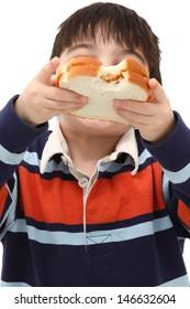 adorable Caucasian Boy Child Eating Peanut Butter Sandwich in Studio