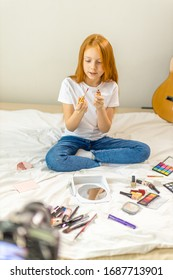 adorable caucasian child with long red hair want to be beauty blogger, show beauty things, use cosmetics
