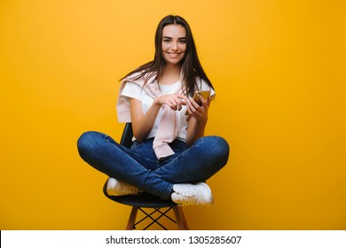 Adorable caucasian woman in casual clothes standing on a chair with a smartphone in her hand looking into camera smiling while buying online isolated over yellow background.