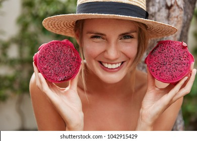 Adorable cheerful young woman glad to spend unforgettable summer holidays in tropics, keeps dragon fruit in hands, eats citrus tropical fruit to keep fit and healthy. People and nutrition concept