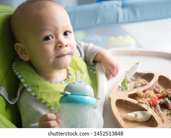 Adorable cheerfully cute 11 months old baby mixed race Asian Caucasian boy eating with BLW method (Baby Led Weaning) and use straw sippy cup for water self-feeding, food for children, BLW method, eat