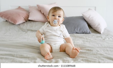 Adorable child with beautiful blue eyes is sitting on the bed sucking on the dummy. Happy cute kid. Pillows on the bed.