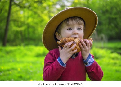 Adorable child biting into a croissant