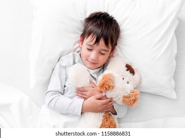 Adorable child boy holding his favourite plush toy while sleeping, view from above
