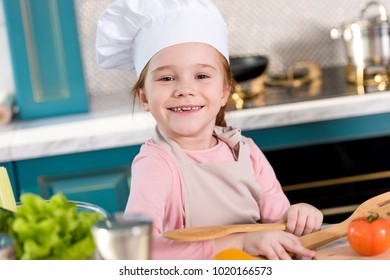 adorable child in chef hat and apron smiling at camera while cooking in kitchen
