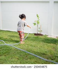 Adorable child girl helping her parents watering the plant at home