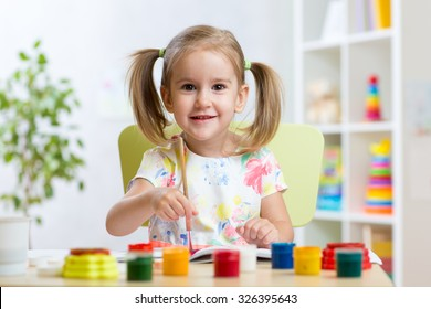 adorable child girl painting with colourful paints