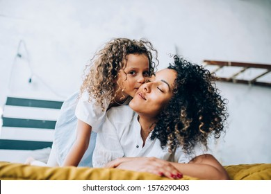 Adorable child hugging and kissing cheek of ethnic glad woman with curly hairstyle in casual wear relaxing in bedroom at home looking at camera