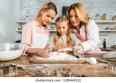 adorable child with mother and grandmother making dough with flour and egg together at home