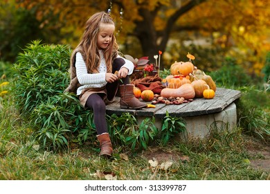 Adorable child playing in autumn park with sweet autumn decoration.