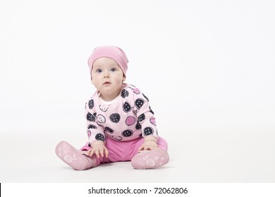 Adorable child sitting on the floor and looking at camera