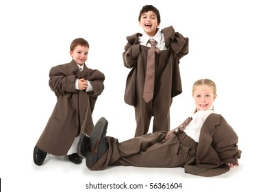 Adorable children in baggy business suits over white.
