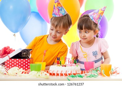 adorable children celebrating birthday party and opening gift box